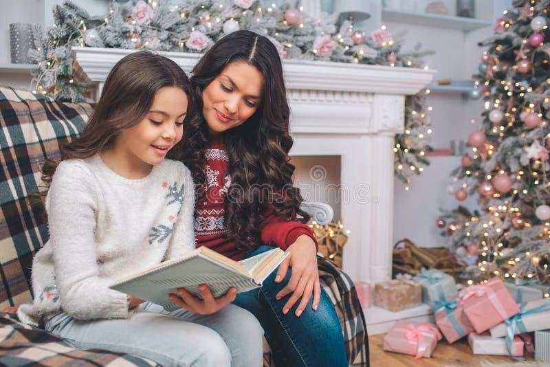 De moeder sittng samen met dochter en bekijkt boek Zij lezen het Het meisje houdt het met beide handen Zij zijn binnen royalty-vrije stock fotografie