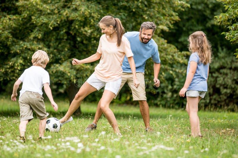 De moeder speelt voetbalvoetbal met familie royalty-vrije stock fotografie