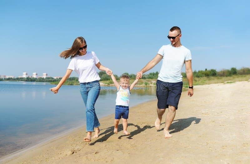 De moeder, de vader en weinig zoon lopen met pret langs rand op zandstrand stock afbeeldingen