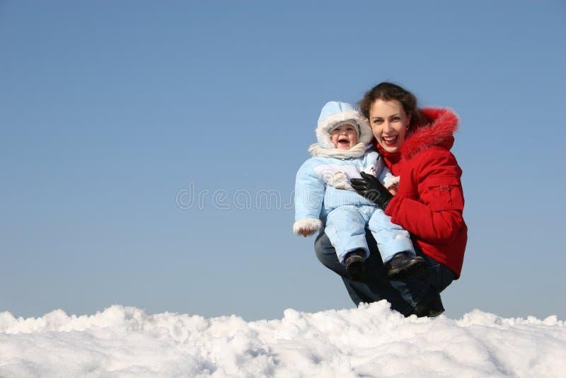 De moeder van de glimlach zit met baby stock afbeelding