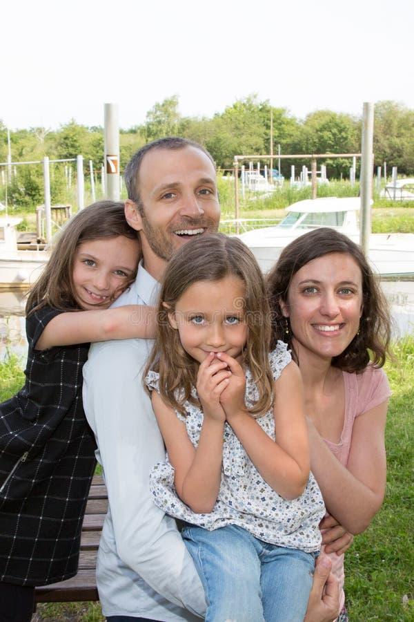 de moeder van de familie in openlucht vader en twee dochters op groene aardachtergrond royalty-vrije stock foto's