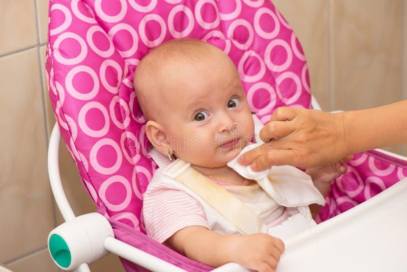 De moeder veegt de mond van de baby af royalty-vrije stock afbeelding