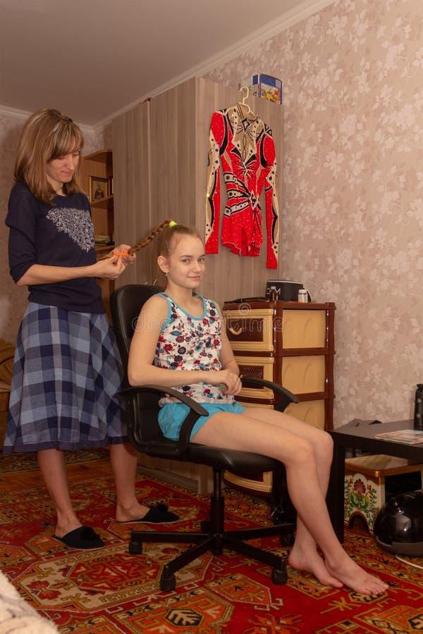 De moeder vlecht haar haar in vlecht 14 éénjarigendochter stock fotografie