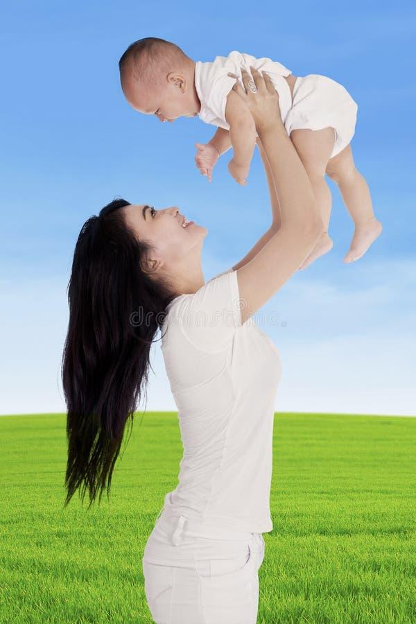 De moeder wierp op haar baby stock fotografie