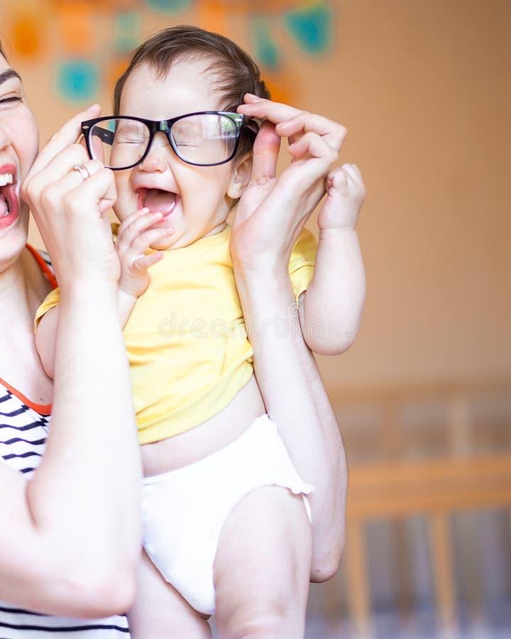 de moeder zette de glazen op baby, lacht de baby gelukkig, spel met moeder stock afbeelding