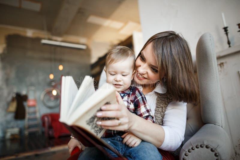 De moeder zit met haar baby en leest een boek Zij glimlacht en bekijkt het stock afbeeldingen