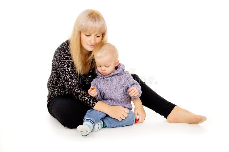 De moeder zit met haar weinig baby stock fotografie