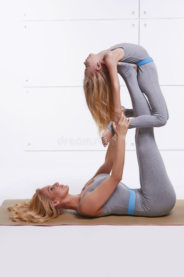 De moederdochter die de fitness van de yogaoefening gymnastiek doen die dezelfde comfortabele in paren gerangschikte vrouw van de stock foto's