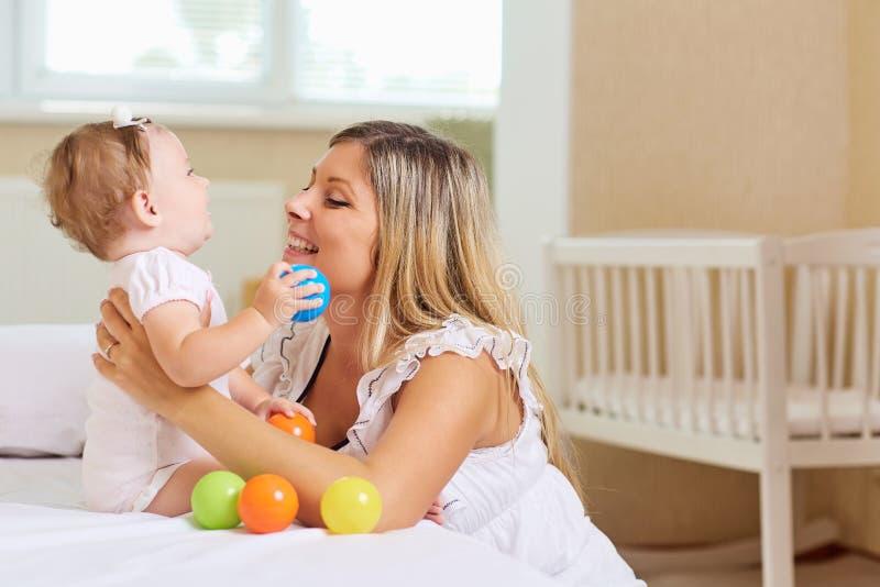 De moederspelen met het babykind op bed in a binnen stock afbeeldingen
