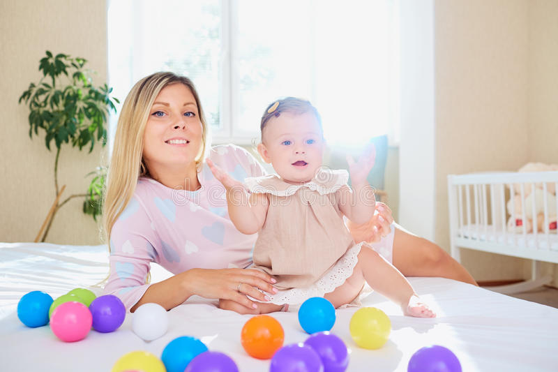 De moederspelen met het babykind op het bed in een ruimte binnen stock afbeelding