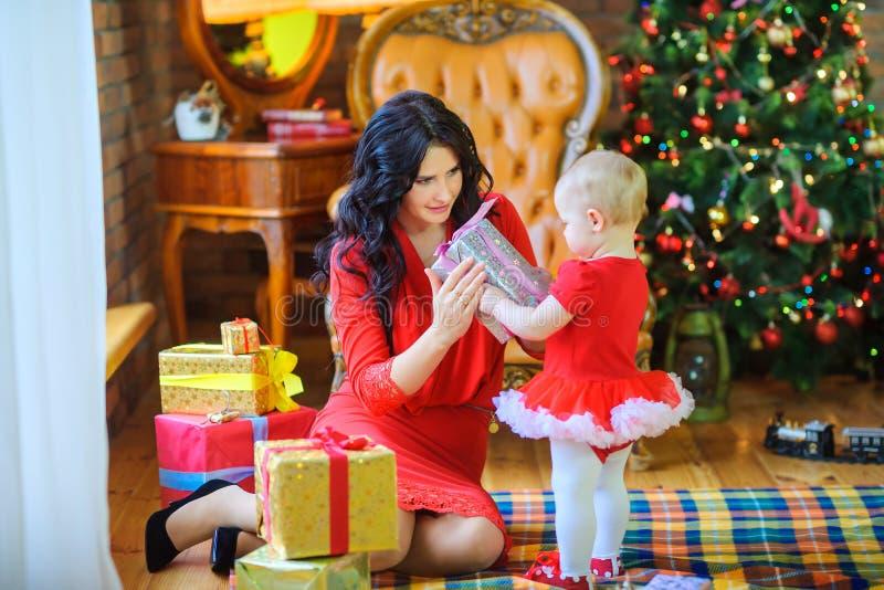 De moederzitting op de vloer dichtbij de Kerstboom geeft een gift aan haar geliefde dochter royalty-vrije stock foto's