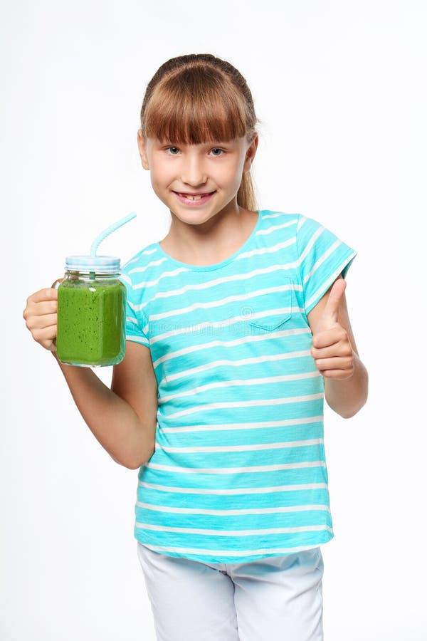De mok van de de kruiktuimelschakelaar van de meisjesholding met groene smoothiedrank stock fotografie
