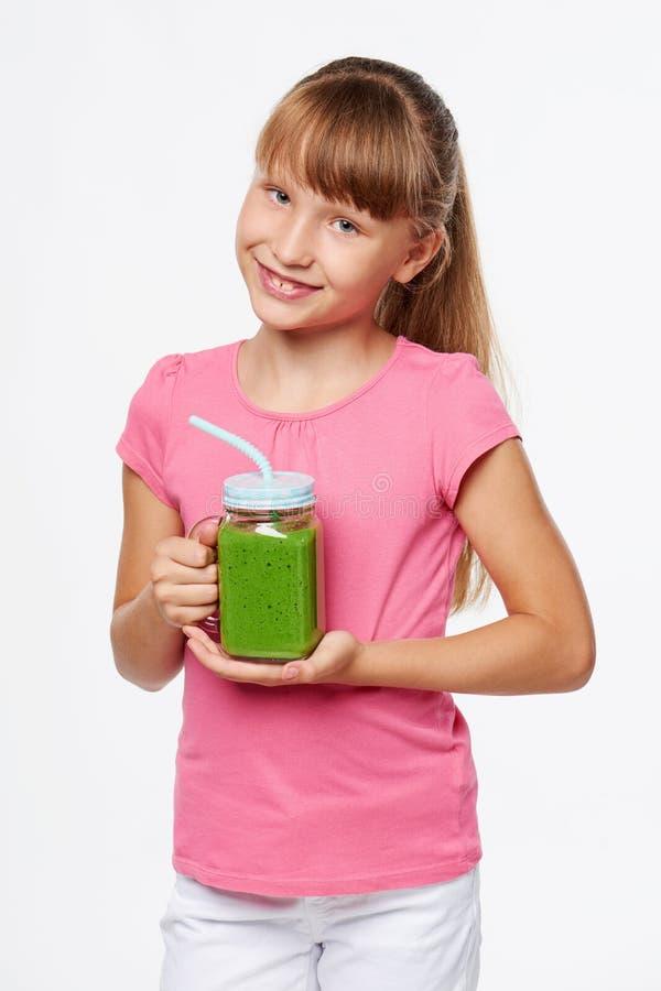 De mok van de de kruiktuimelschakelaar van de meisjesholding met groene smoothiedrank royalty-vrije stock afbeeldingen