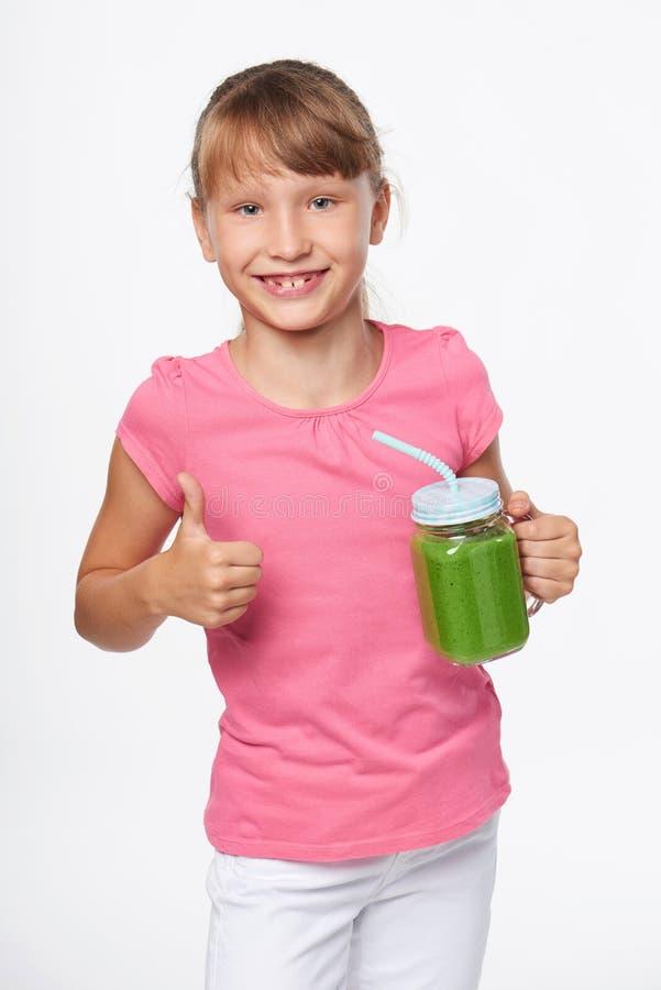 De mok van de de kruiktuimelschakelaar van de meisjesholding met groene smoothiedrank stock afbeelding