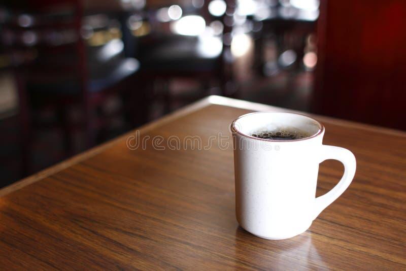 De mok van de koffie op lijst royalty-vrije stock afbeeldingen