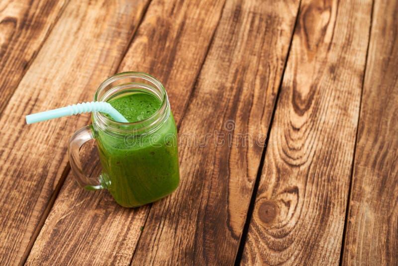 De mok van de kruiktuimelschakelaar met groene smoothiedrank stock afbeeldingen