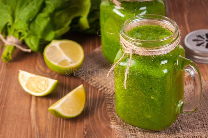 De mokken van de metselaarkruik die met groene spinazie en boerenkoolgezondheid worden gevuld smoothie wervelden stro royalty-vrije stock foto's