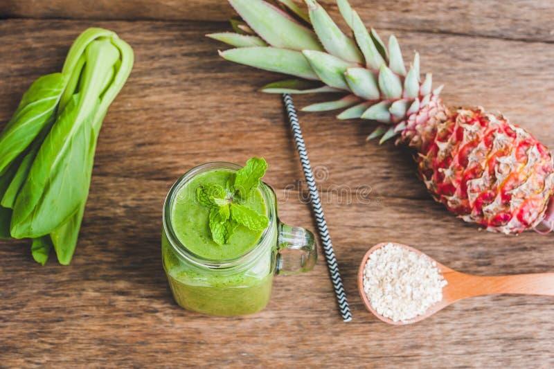De mokken van de metselaarkruik met groene spinazie, banaan en kokosmelkgezondheid smoothie met met een lepel van havermeel op ho royalty-vrije stock foto
