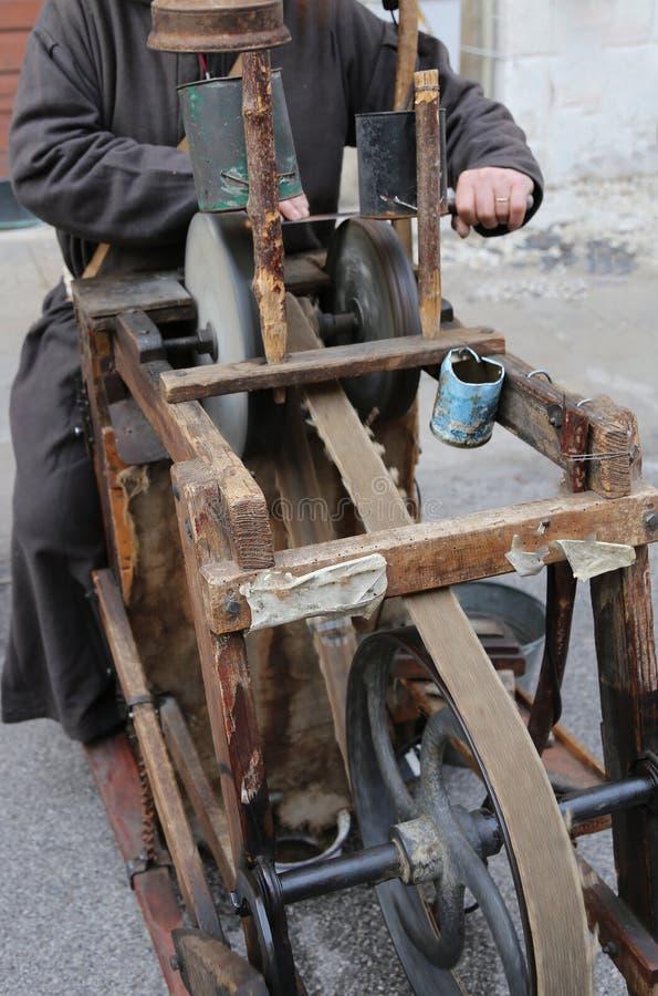 De molen met grote handen scherpt een blad van een mes stock afbeeldingen