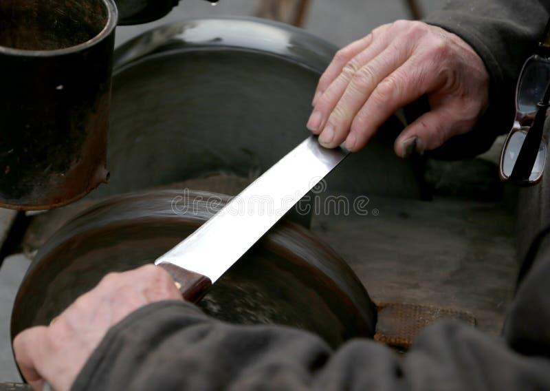 De molen met grote handen scherpt een mes stock foto's