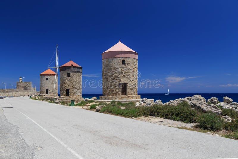 De molens van Rhodos op de achtergrond van de overzeese baai en de haven zonnige dag stock fotografie