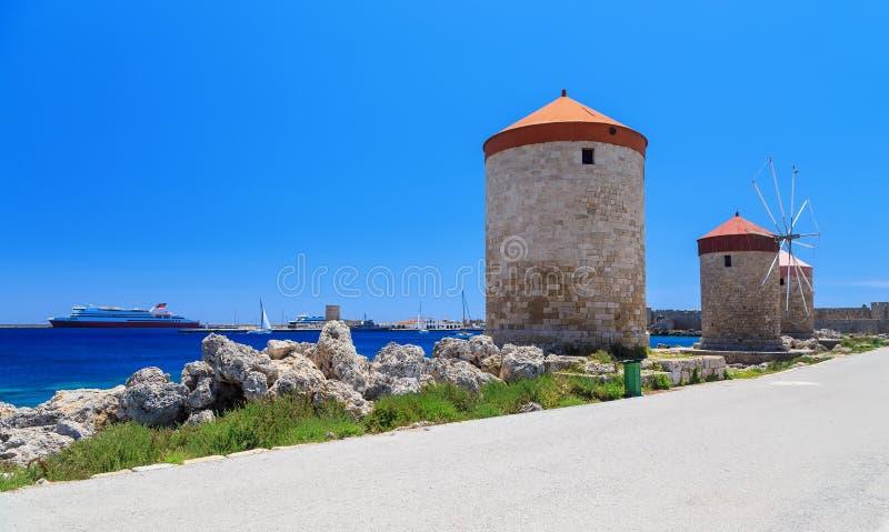De molens van Rhodos op de achtergrond van de overzeese baai en de haven zonnige dag royalty-vrije stock fotografie
