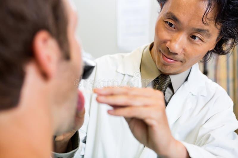 De Mond van artsenexamining patient in het Ziekenhuis stock foto