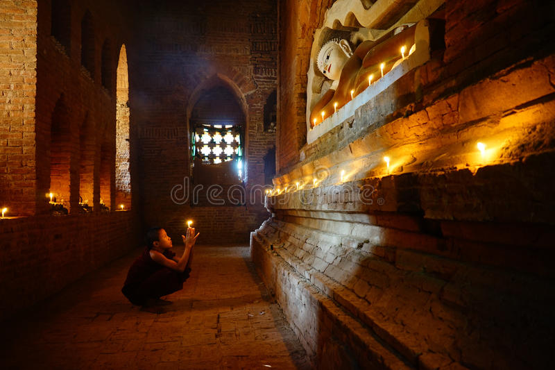De monnik bidt met kaars in Bagan, Myanmar stock foto