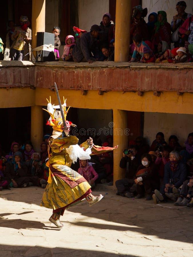 De monnik in hertenmasker met ritueel zwaard voert godsdienstige geheimzinnigheid dans van Tibetaans Boeddhisme uit stock foto