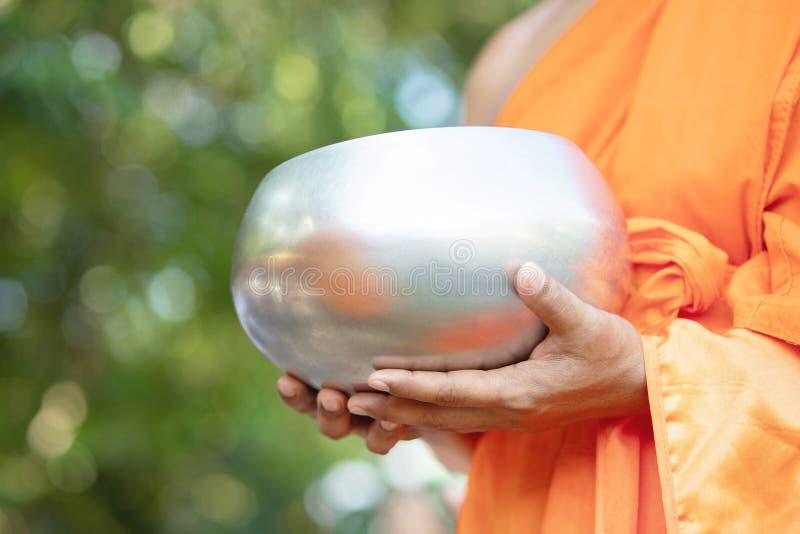 De monnik met handholding geeft aalmoeskom die uit het dienstenaanbod in de ochtend bij Boeddhistische tempel, de Plaatstra van d royalty-vrije stock foto