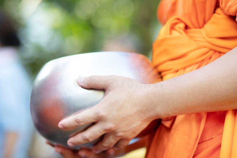 De monnik met handholding geeft aalmoeskom die uit het dienstenaanbod in de ochtend bij Boeddhistische tempel, de Plaatstra van d stock foto's