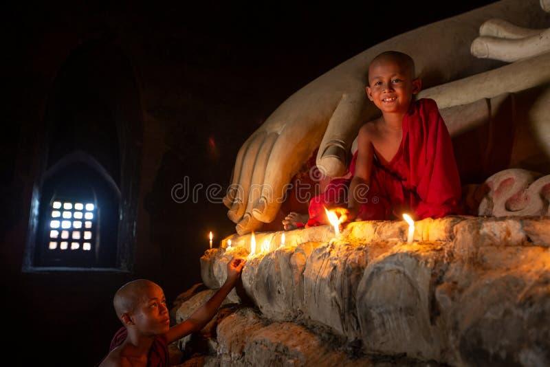 De monnik in de oude stad van Bagan bidt een standbeeld van Boedha met kaars stock afbeelding