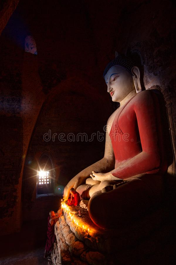 De monnik in de oude stad van Bagan bidt een standbeeld van Boedha met kaars royalty-vrije stock afbeelding
