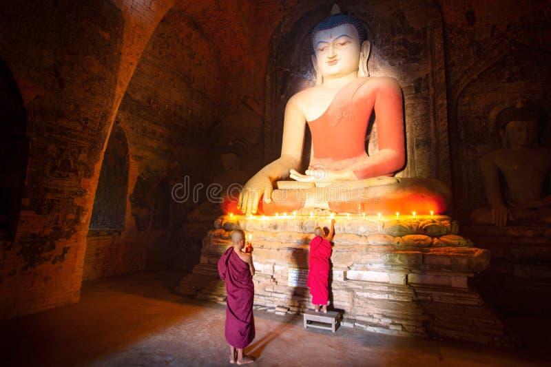 De monnik in de oude stad van Bagan bidt een standbeeld van Boedha met kaars royalty-vrije stock afbeeldingen