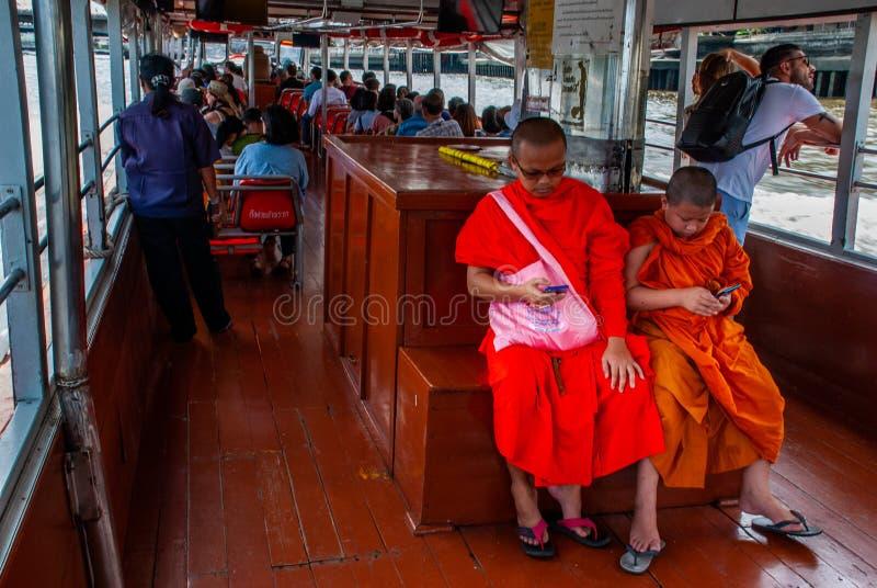 De monniken en de beginners letten op mobiele berichten tijdens Chao Phraya Express Boat Ride stock afbeelding