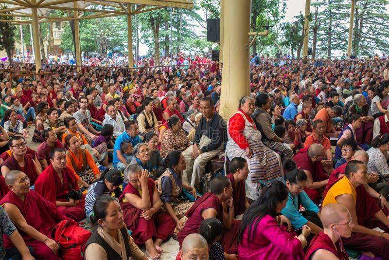 De monniken en tibetan mensen die aan zijn Heiligheid luisteren 14 Dalai die Lama Tenzin Gyatso het onderwijs in zijn woonplaats  stock foto's