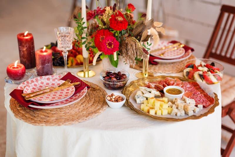 De montages van de luxelijst voor het fijne dineren met kaarsen en glaswerk, mooie vage achtergrond Voor gebeurtenissen, huwelijk stock foto