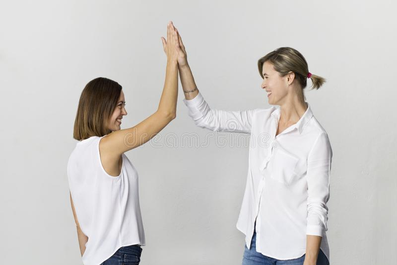 De mooie aantrekkelijke grappige ontspannen onbezorgde meisjes begroeten in witte overhemd en jeans royalty-vrije stock foto