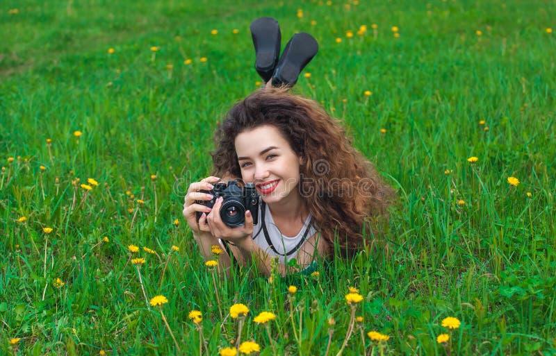 De mooie, aantrekkelijke meisje-fotograaf met krullend haar houdt een camera en het liggen op het gras met bloeiende paardebloeme stock afbeeldingen