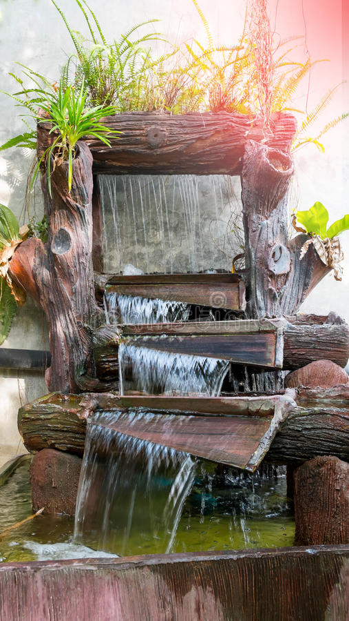 De mooie aard in tuin met waterval op steenmuur Fou stock afbeelding