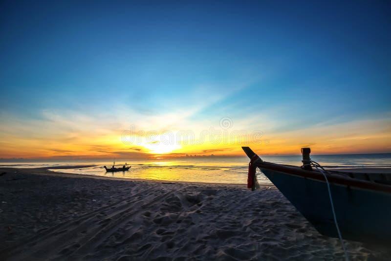 De mooie achtergrond van de zonsondergangzonsopgang op het strand met silhouetboot in de voorgrond stock afbeelding