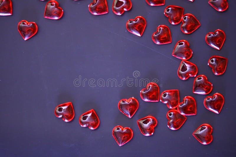 De mooie achtergrond van de valentijnskaartendag met rode harten op donkere achtergrond stock foto's