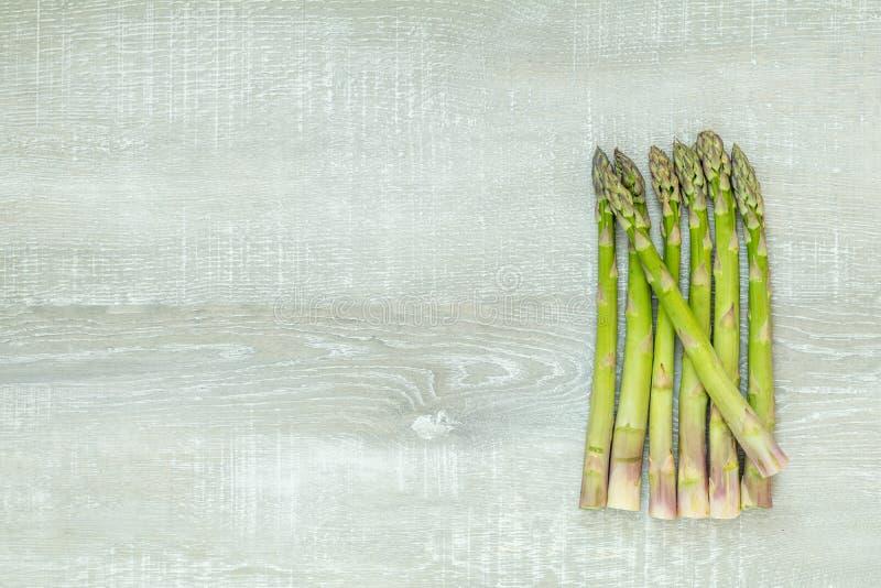 De mooie achtergrond van de voedselkunst Aspergespruiten op lichte houten royalty-vrije stock foto's