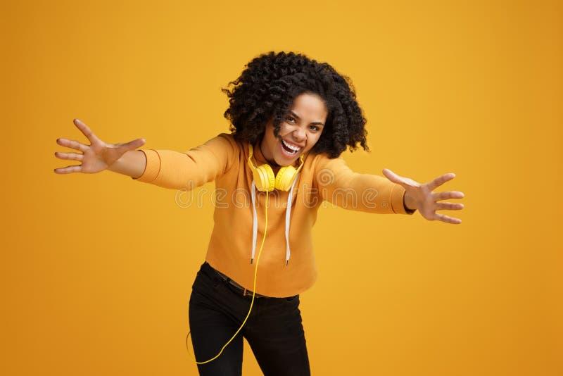De mooie Afrikaanse Amerikaanse jonge vrouw met heldere glimlach kleedde zich in vrijetijdskleding en hoofdtelefoons klaar over v royalty-vrije stock afbeeldingen