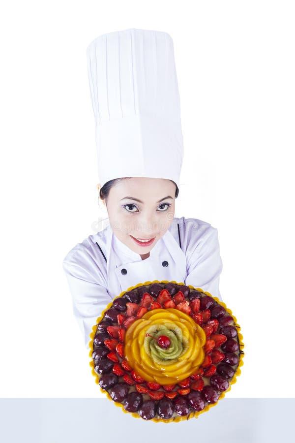 De Aziatische chef-kok dient dessert op wit stock afbeeldingen