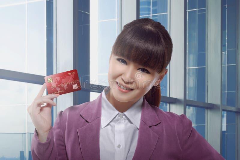 De mooie Aziatische creditcard van de bedrijfsvrouwenholding royalty-vrije stock afbeeldingen