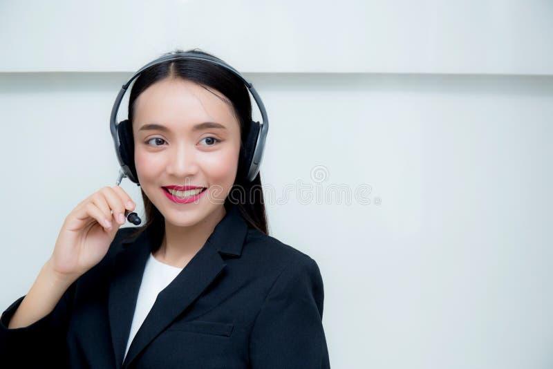 De mooie Aziatische dienst die van de vrouwen glimlachende klant op hoofdtelefoon spreken stock fotografie