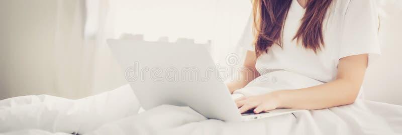 De mooie Aziatische jonge vrouw die van de bannerwebsite bij bed het gebruiken plaatsen royalty-vrije stock foto's