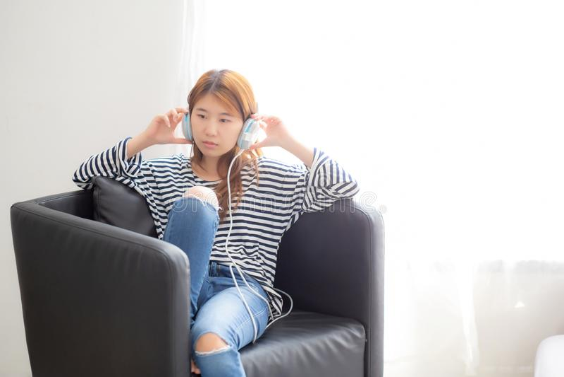 De mooie Aziatische jonge vrouw geniet van en de pret luistert muziek met hoofdtelefoonzitting op stoel in de slaapkamer stock foto's