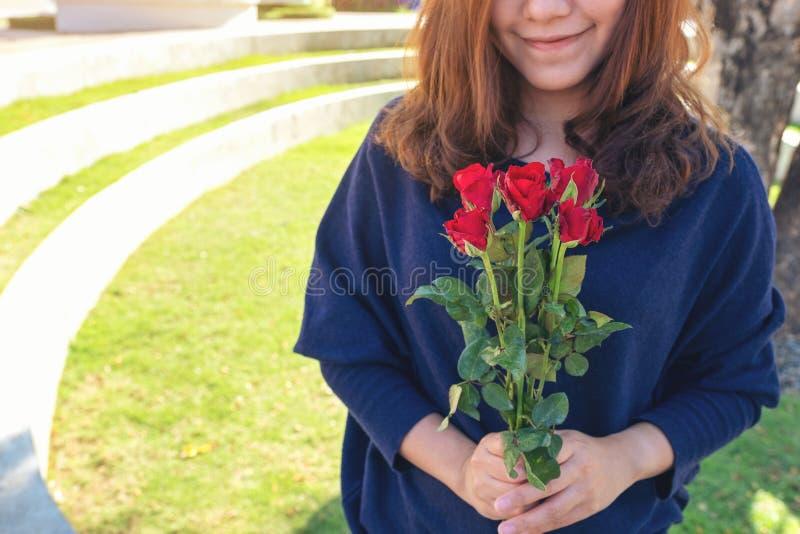 De mooie Aziatische vrouw die rode rozen houden bloeit met gevoel gelukkig op de dag van Valentine stock afbeeldingen
